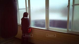 窓の前に立っている人の写真・画像素材[1119792]