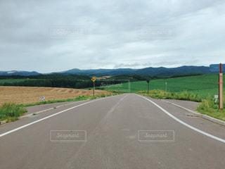 広い道路と山と空の写真・画像素材[1089869]