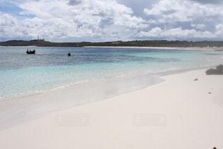 水の体の横にある砂浜のビーチ - No.1089824