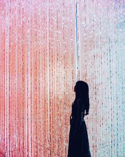 カーテンの前に立っている人の写真・画像素材[2141960]
