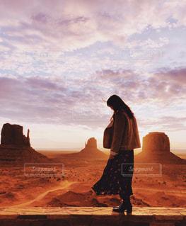 夕日の前に立っている男の写真・画像素材[2141987]
