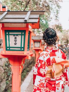 建物の前に立っている赤いドレスを着た人の写真・画像素材[2142119]