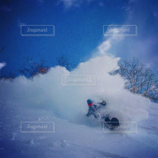 雪に覆われた斜面をスキーに乗る人の写真・画像素材[1090330]