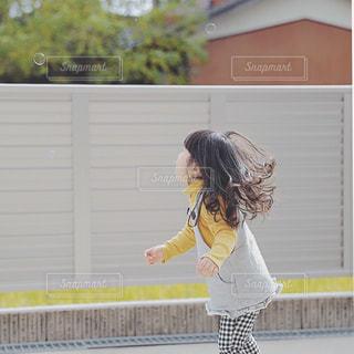 建物の前に立っている女の子の写真・画像素材[1130648]