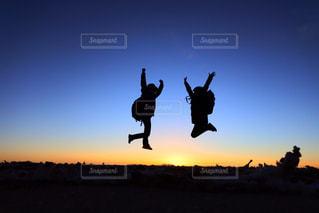 バック グラウンドで夕日を持つ人の写真・画像素材[1092883]