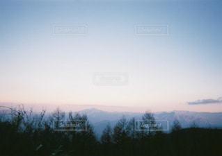 バック グラウンドで夕日を持つ人の写真・画像素材[1851540]