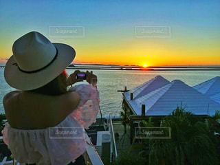 夕焼けの写真を撮る女子の写真・画像素材[1092818]