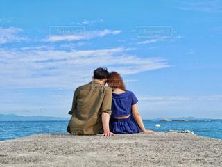 海辺に座っているカップルの写真・画像素材[1276119]
