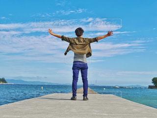 水の体の横に立っている人の写真・画像素材[1432131]
