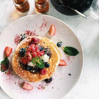 テーブルの上に食べ物のプレートの写真・画像素材[1098734]