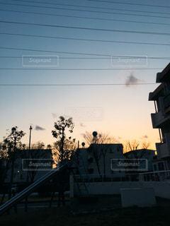 背景の夕日と建物の写真・画像素材[1103390]