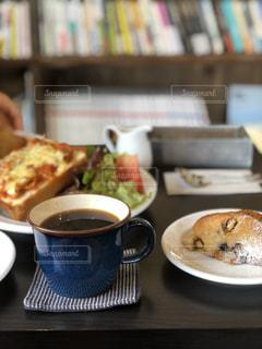 食品やコーヒー テーブルの上のカップのプレートの写真・画像素材[1120913]