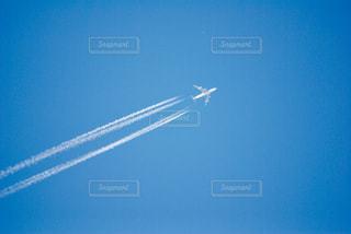 青い空を飛んでいるジェット機の写真・画像素材[1099418]