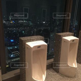 男子トイレの便器と夜景の写真・画像素材[1098489]