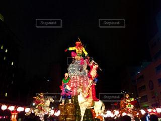 夜ライトアップされたクリスマス ツリーの横に立っている人々 のグループの写真・画像素材[1100016]