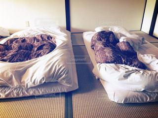 ベッドの上で眠っている人の写真・画像素材[1111500]