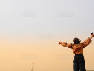 空に向かって手をあげる人の写真・画像素材[1104683]