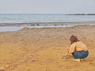 砂浜の上に座っている人の写真・画像素材[1104701]