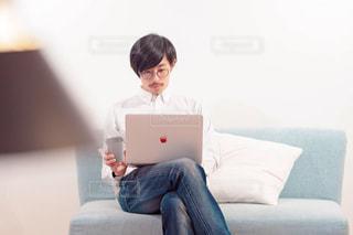 ノート パソコンとソファに座る人の写真・画像素材[1817327]
