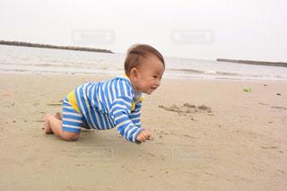 ビーチの砂の上でハイハイする赤ちゃんの写真・画像素材[1107273]