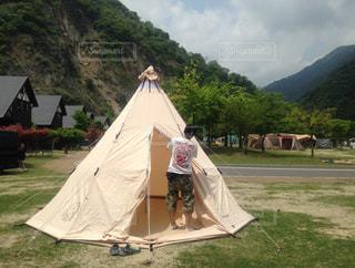 背景の山にテントの写真・画像素材[1107342]