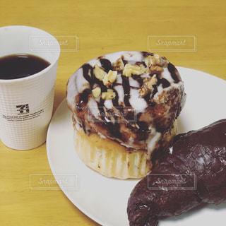 コーヒー カップの横にある皿の上のケーキの一部 - No.1148558