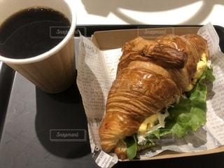 近くにサンドイッチとコーヒーのカップのアップの写真・画像素材[1153152]