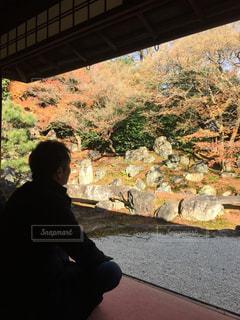 建物の前に座っている男の写真・画像素材[1107057]