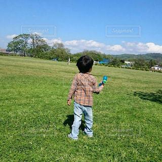 緑豊かな緑のフィールドに立っている間凧の飛行少年の写真・画像素材[1107306]