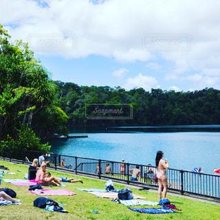 水の体の横にあるベンチに座っている人々 のグループの写真・画像素材[1109788]