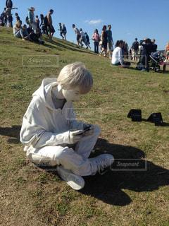 草の上に座っている男にフィールドが覆われています。の写真・画像素材[1125652]