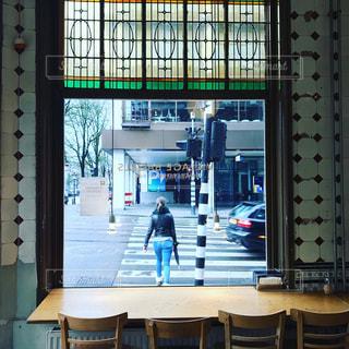 窓の前で机に座っている人の写真・画像素材[1113297]