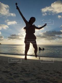 海辺でジュリエットの飛び跳ねる女性の写真・画像素材[1115009]