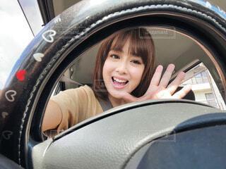 ハンドル越しに手を振る可愛い女性の写真・画像素材[4668469]