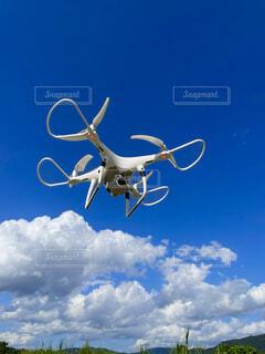 青空に飛ぶドローンの写真・画像素材[4803157]