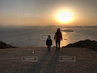 海をバックに夕日を眺める親子の写真・画像素材[1114600]