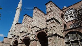 背の高い建物の前に時計塔と石造りの教会の写真・画像素材[1121367]