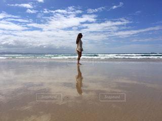 水の体の近くのビーチに立っている人の写真・画像素材[1117309]
