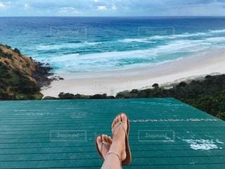 水の体の近くのビーチに座っている人の写真・画像素材[1121694]