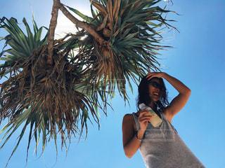 ヤシの木の前で携帯電話で話す人の写真・画像素材[1121697]