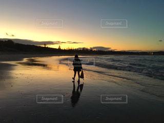 水の体の横にビーチの上を歩く男 - No.1121700