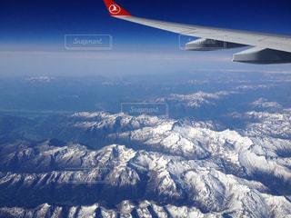 雪の覆われた山上空を飛ぶ飛行機の写真・画像素材[1116734]