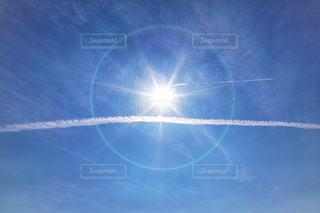 陽光と飛行機雲の写真・画像素材[1585600]