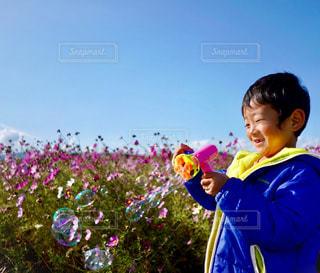 青空に凧を持っている人の写真・画像素材[1625967]