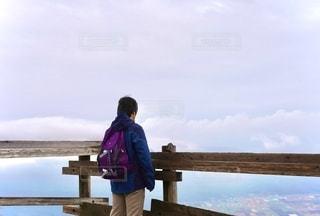 水域の前のベンチに座っている人の写真・画像素材[2699232]