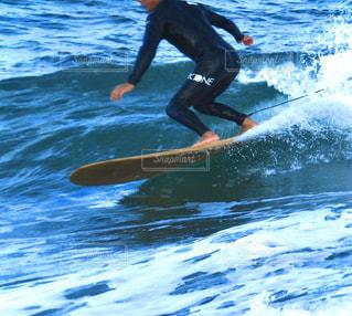 水の中のサーフボードで波に乗っている男の写真・画像素材[2820531]