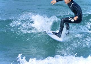 海のサーフボードで波に乗っている男の写真・画像素材[2820530]