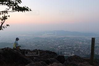 山を背景に水の体の隣に立っている男の写真・画像素材[3609456]