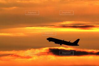 朝焼けのを飛んでいる飛行機の写真・画像素材[1122809]