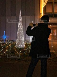 クリスマス ツリーの前に立っている男性の写真・画像素材[1668872]